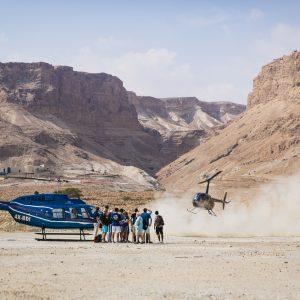 קבוצת אנשים בטיול יוקרה במדבר עם מסוק נוחת במדבר