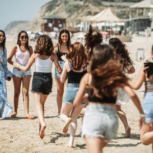 ילדות רצות בחוף לקראת החברה שלהן שחוגגת בת מצווה בהפתעה