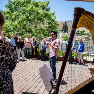 ארז לנדאו מדריך טיולים בכיר מדריך קבוצה בירושלים וברקע מנגנת אישה בנבל