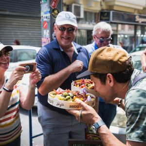 ארז לנדאו מדריך טיולים בכיר עם מגש אוכל ממעדניית יום טוב מגיש לקבוצה