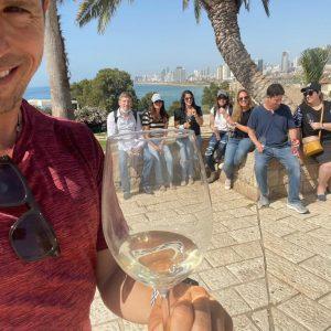 ארז לנדאו מדריך טיולים בכיר עם כוס יין ומאחוריו קבוצה בסיור מודרך בתל אביב