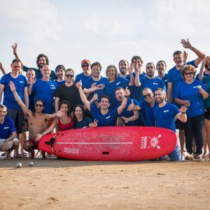 קבוצת אנשים שמצטלמים יחד עם גלשן בים